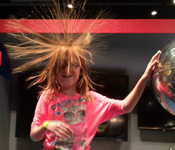 photo of student touching Van Der Graff generator